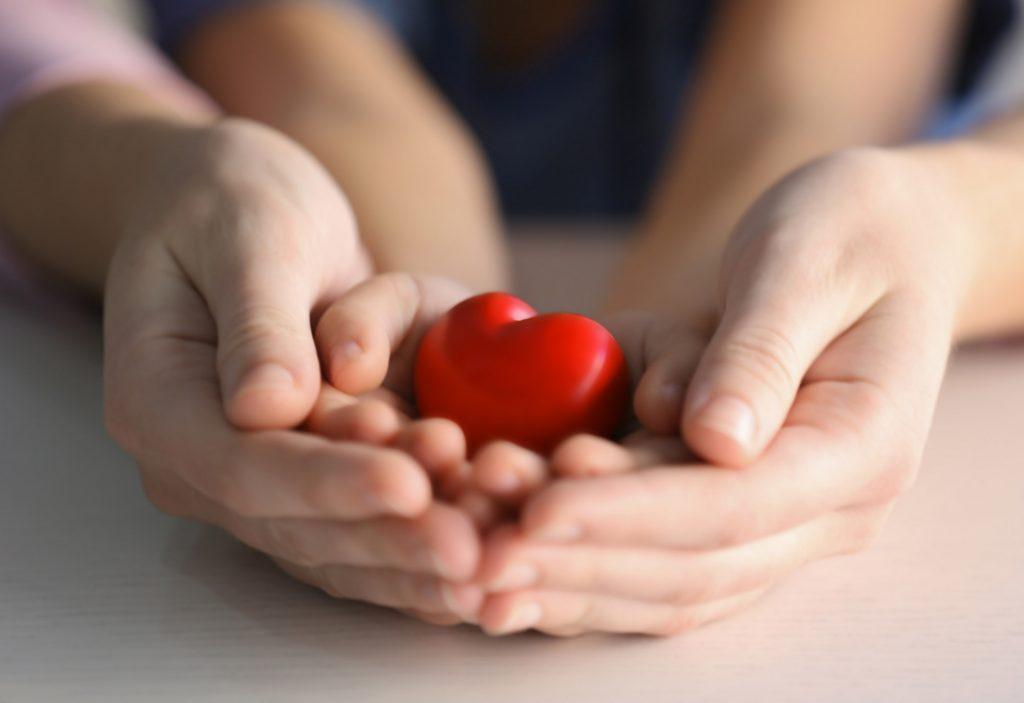 Child and adult person holding red heart, closeup. Adoption concept